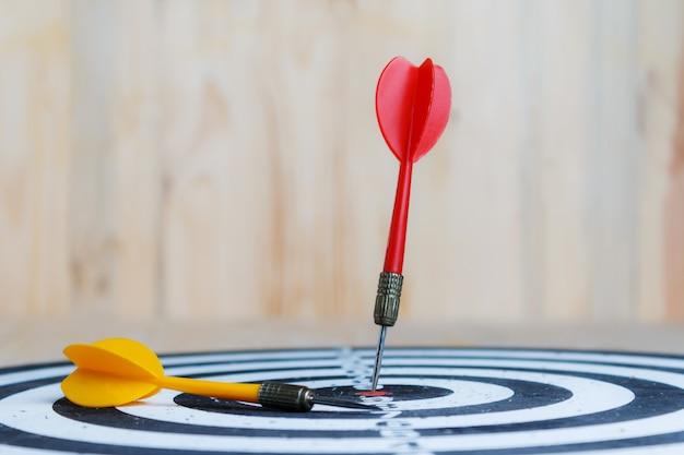 La flèche rouge du fléchette a atteint la cible centrale du jeu de fléchettes et de la flèche jaune