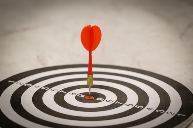 La flèche rouge de la fléchette frappe au centre de la cible.