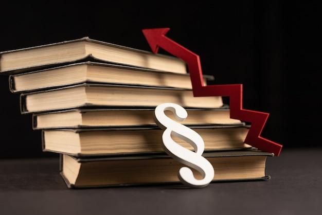 Flèche rouge, livres et signe de paragraphe. concept d'investissement dans l'éducation et la connaissance