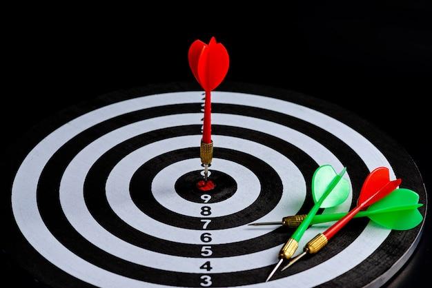 Flèche rouge et verte fléchette frappant le centre cible est un jeu de fléchettes isolé