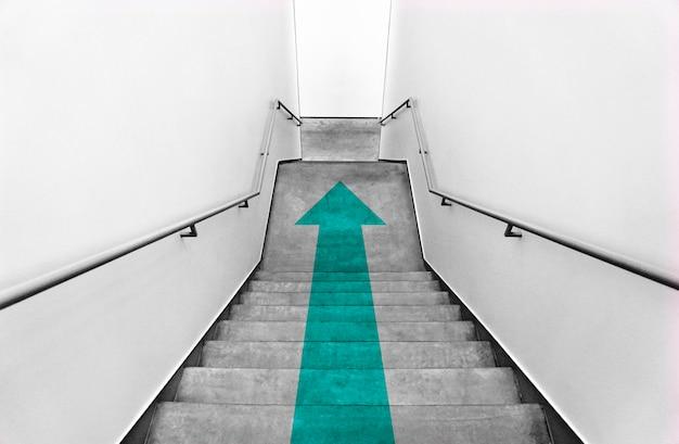 Flèche sarcelle sur les escaliers gris