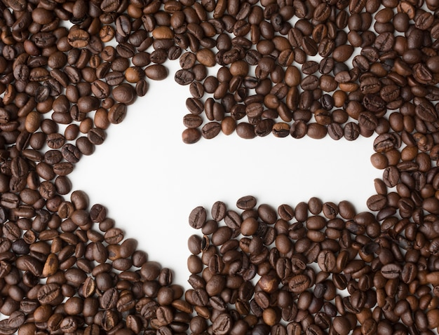 Flèche à travers les grains de café pointant vers la gauche