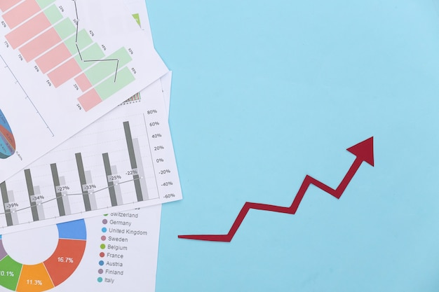 Flèche vers le haut de la croissance, graphiques et tableaux sur bleu. la réussite des entreprises