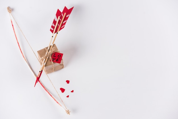 Flèches d'amour avec un arc et une boîte cadeau sur une table blanche