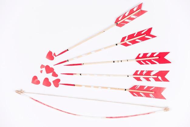 Flèches d'amour visant de petits coeurs rouges