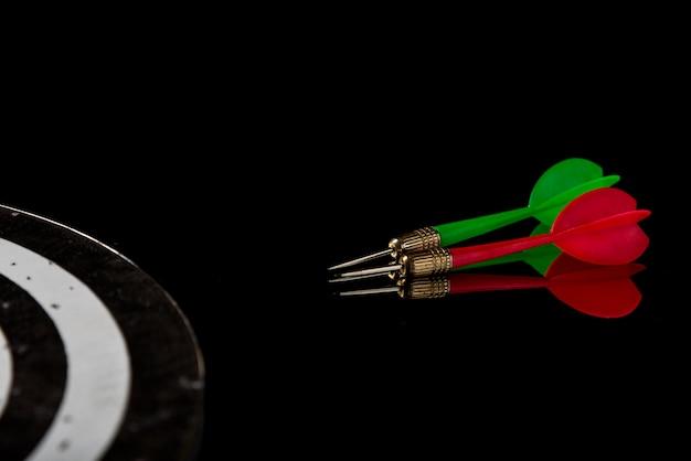 Flèches de couleur sur fond noir et cible. atteindre la cible