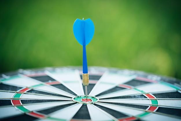 Flèches de fléchettes bleues frapper dans le centre cible du jeu de fléchettes avec fond de nature verdoyante.