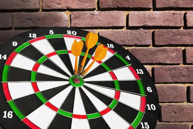 Flèches de fléchettes dans le centre de la cible