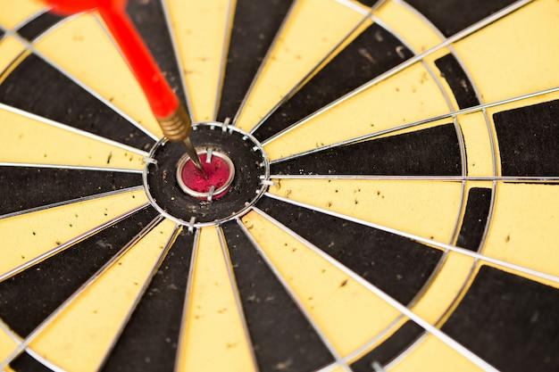 Flèches de fléchettes rouges dans le centre de la cible