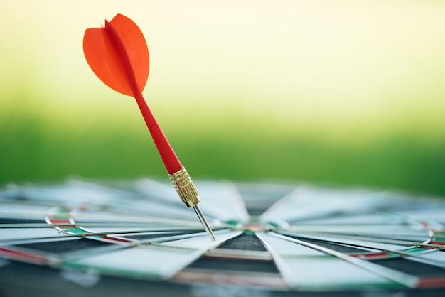 Flèches de fléchettes rouges frappant dans le centre cible du jeu de fléchettes avec fond de nature verdoyante.
