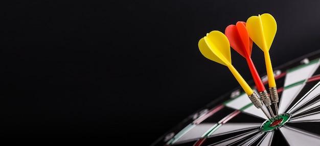 Flèches de fléchettes rouges et jaunes au centre du jeu de fléchettes. concept de succès, de buts et d'objectifs.
