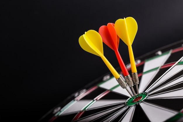 Flèches de fléchettes rouges et jaunes au centre du jeu de fléchettes.