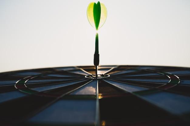 Flèches de fléchettes vertes au centre de la cible sur fond de ciel. objectif commercial ou objectif de réussite et concept de gagnant.