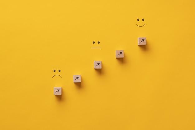 Flèches pointant d'une expression triste vers une expression heureuse - image conceptuelle de la croissance personnelle et de l'aspiration.