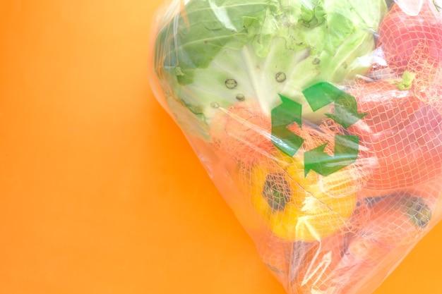 Les flèches recyclées signent sur un sac à provisions avec des légumes