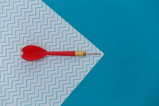 Fléchette en plastique rouge avec pointe en métal sur fond bleu pastel avec espace de copie.