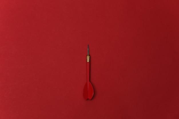 Fléchette en plastique rouge avec pointe en métal sur fond rouge.