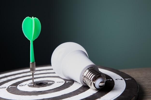 Des fléchettes au centre de la cible et une ampoule. créativité conceptuelle