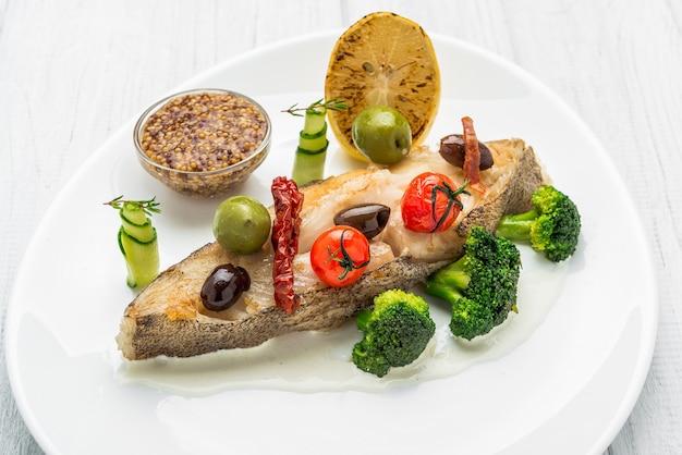 Flétan frit avec des légumes et de la moutarde, sur la plaque