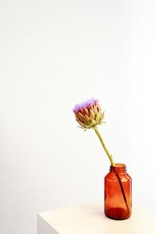 Fleur d'artichaut unique dans un vase en verre sur un mur blanc, mise au point sélective