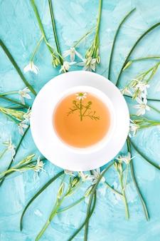 Fleur autour d'une tasse de thé à la camomille sur fond bleu.