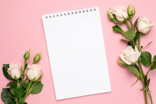 Fleur de belles roses blanches et cahier sur la vue de dessus de fond rose