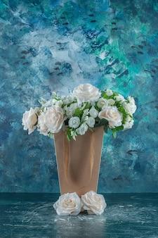 Fleur blanche artificielle dans un paquet, sur fond bleu.