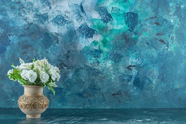 Fleur blanche artificielle dans un vase, sur fond bleu.