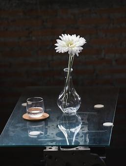 Fleur blanche dans un vase sur fond de brique de table en verre