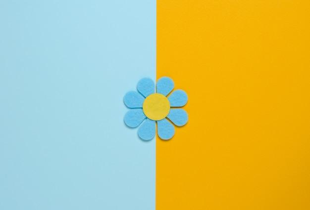 Fleur bleue en feutre sur fond bleu et orange.