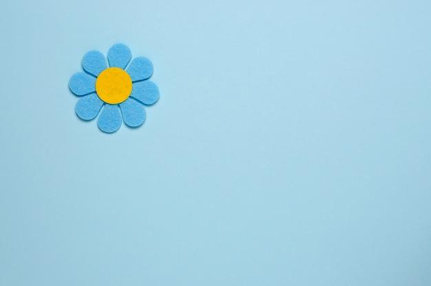 Fleur bleue en feutre sur fond bleu.