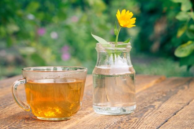 Fleur de calendula avec une tige dans un bocal en verre et une tasse de thé vert sur des planches de bois.