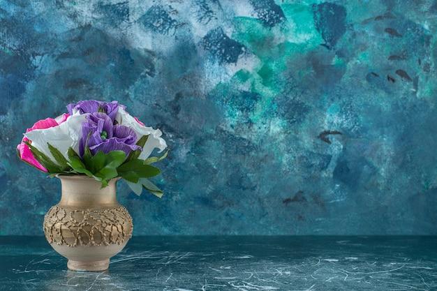 Fleur colorée artificielle dans un vase, sur fond bleu.