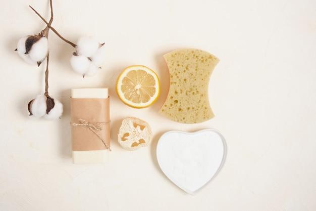 Fleur de coton, citron, luffa, savon et bicarbonate de soude pour le ménage. concept de mode de vie écologique, zéro déchet, vue de dessus de l'espace de copie de nettoyage écologique