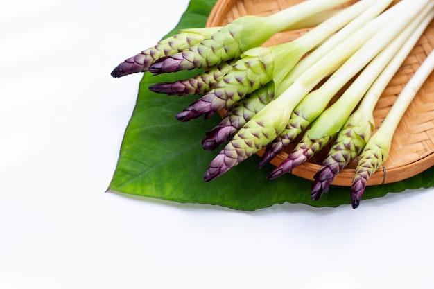 Fleur de curcuma sessilis dans un panier en bambou sur fond blanc.