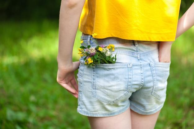 Fleur dans une grande poche de pantalon jeans, concept d'été