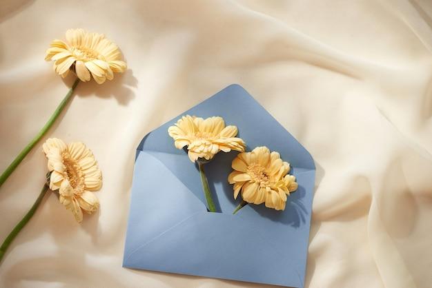 Fleur dans et hors de l'enveloppe sur le fond de tissu clair