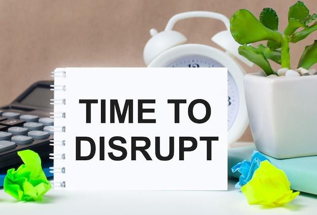 Fleur dans un pot, calculatrice, réveil blanc, morceaux de papier multicolores et un cahier blanc avec le texte time to disrupt sur le bureau.