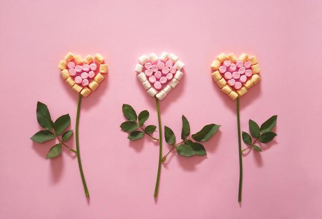 Fleur en forme de coeur sur fond rose.