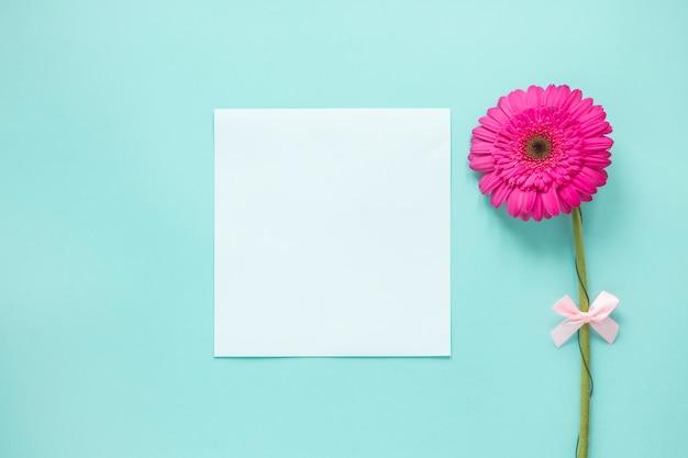 Fleur de gerbera rose avec du papier vierge sur la table