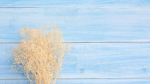 Fleur de gypsophile sec sur une table en bois bleue.
