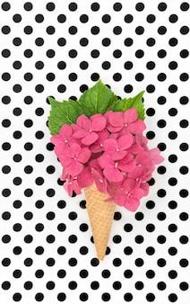Fleur d'hortensia rose en cornet de gaufre de crème glacée sur fond de pois