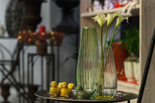 Fleur jaune avec une longue tige dans un vase sur un support avec des oiseaux artificiels