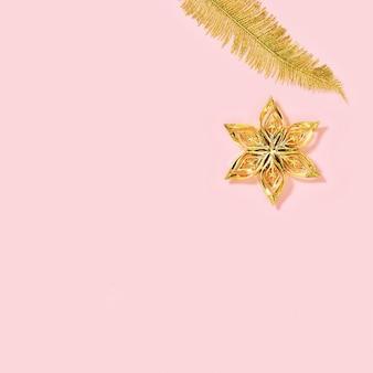Fleur de jouets de nouvel an doré métallique et feuilles de palmier sur rose avec espace copie