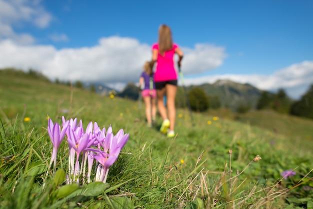 Fleur de montagne rose avec des filles qui courent dans le pré