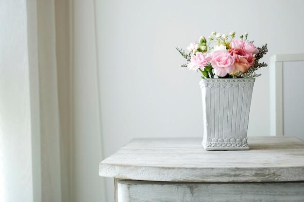 Fleur d'oeillet en pot de ciment sur armoire vintage à la chambre