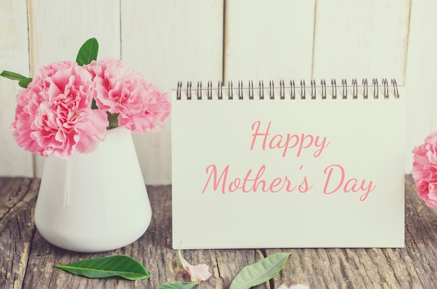 Fleur d'oeillet rose avec texte heureux jour de mère sur papier carte blanc avec ton vintage