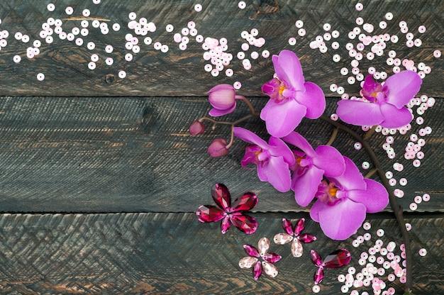 Fleur d'orchidée, cristaux et paillettes sur le vieux fond en bois