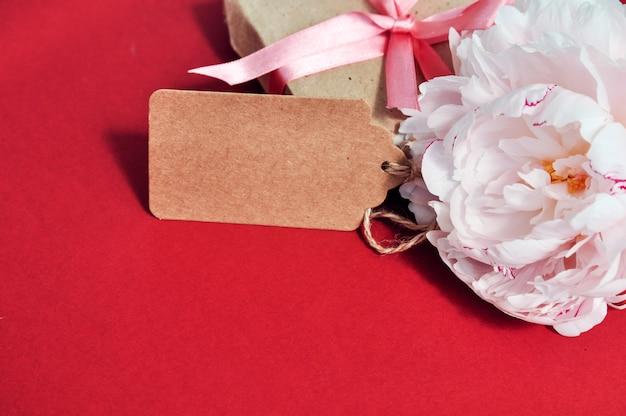 Fleur de pivoine rose à côté de la boîte-cadeau sur le rouge.