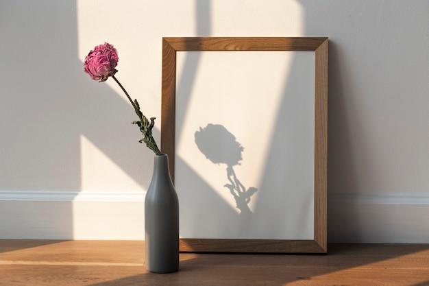 Fleur de pivoine rose séchée dans un vase gris par un cadre en bois sur le sol